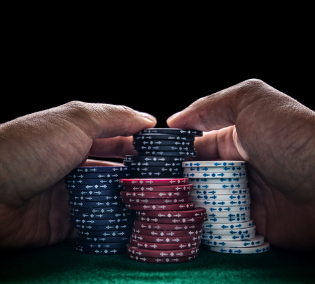 Stack of poker chips and two hands on green table Stock Photo