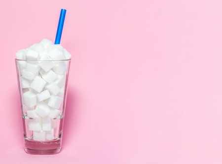 Glass full of sugar cubes - unhealthy diet concept. Imagens