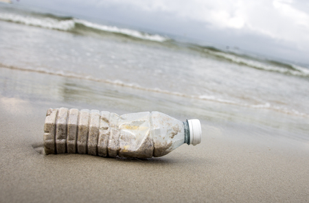 Enviromental pollution - plastic bottle on a beach.
