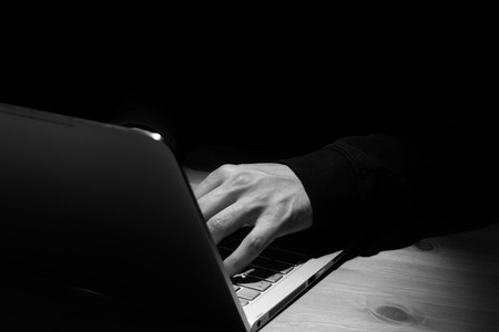 Anonymous person with notebook in the dark.