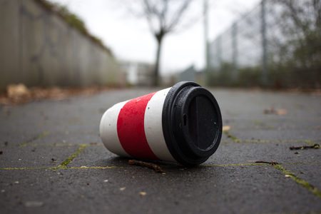 Used Coffee mug at sidwalk as symbol for pollution. Imagens