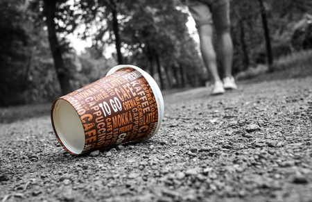 Used Coffee mug at forest path as symbol for pollution.