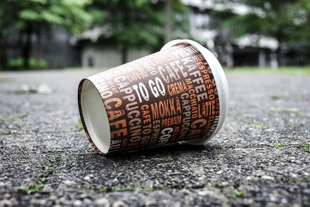Used Coffee mug at sidewalk as symbol for pollution.