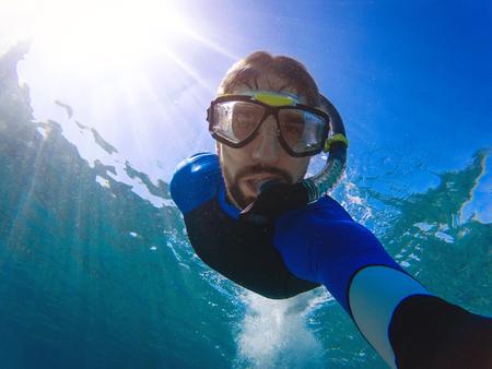 Young man takes underwater selfie. Imagens