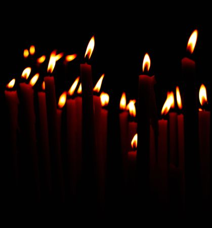 candle flames in church aganins black background photo