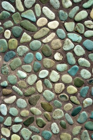 closeup of decorated garden pavement with blue stones in brown sand