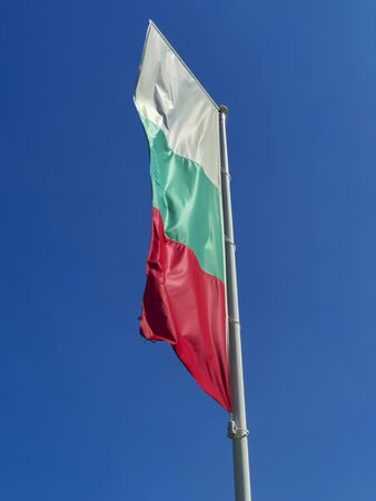 Bulgarian flag waving on blue sky background. The location is Obzor, Bulgaria. Flag of Bulgaria against the clear sky. Stock fotó
