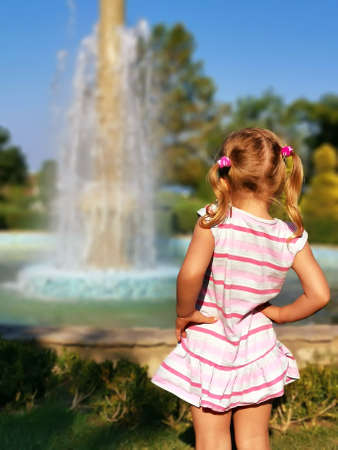 Preschooler little girl watching fountain rear view. Young female child enjoy being outside in summertime. Curiosity blonde looking at splashing droplets. enjoyment of holidays. Pretty kid photography 免版税图像