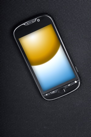 Smart Phone on Dark Carbon Background. Yellow-Blue Display Image. Modern Cellphone. Vertical Photo. photo