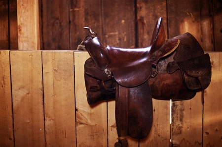 Brown Leather Saddle - Western Style Saddle on the Wood Fence. Horizontal Photo. photo
