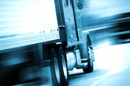 Semi Truck in Motion. Piste semi excès de vitesse sur l'autoroute américaine. Mouvement flou. Tons bleus. Transports et Collection de photos Spedition. Banque d'images - 10645091