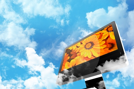 Techniek en Natuur Thema. Moderne Computer display tussen de wolken. Bewolkte blauwe hemel. Oranje bloemen op het scherm.
