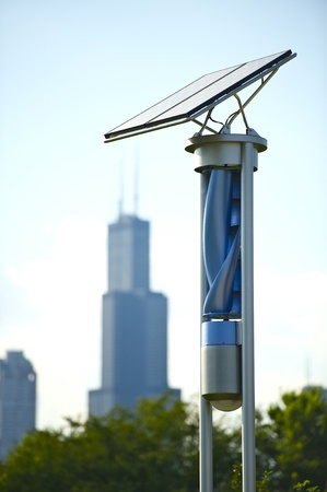 alternative energy sources: Small Creative Solar and Wind Energy Generator. Chicago Downtown in the Background. Small Solar Panel on the Top and Spiral Wind Generator Below. Alternative Energy Sources in Chicago, Illinois, USA.