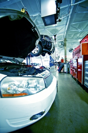 In the Auto Service. Damaged White Vehicle with Open Hood. Large Warehouse / Dealer Service Area.