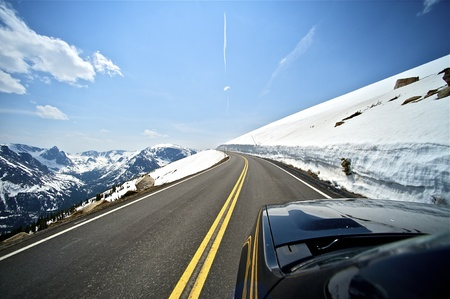 winter road: Riding Colorado Mountain Road. Plenty of Sun and Snow. Clean and Dry Road. Mountains Landscape. Stock Photo