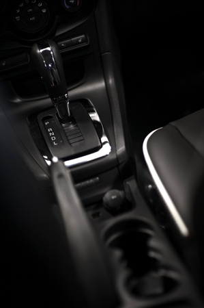Modern Driving. Dark Vehicle Interior - Central Console with Cup Holders, Seats and Automatic Transmission Stick Shift. Vertical Photo. Vehicle Interiors Photo Collection Stock Photo - 10724625
