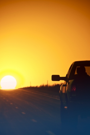 thru: Sunset Outback Highway. Pickup on the Highway - Sunset. Vertical Photo. Stock Photo