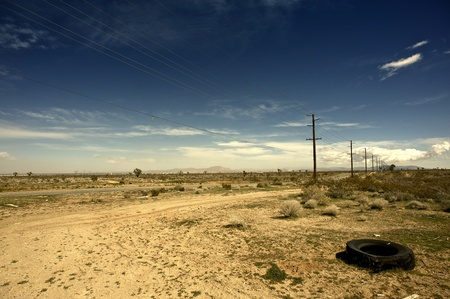 Outback California USA - California Suburbs Desert Landscape with Old Broken Tire on the Road Side. photo