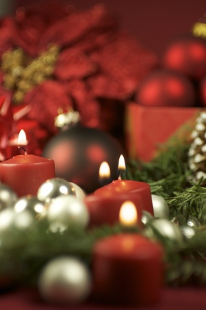 burning time: Christmas Time Decoration. Beautiful Composition with Red Burning Candles and Christmas Ornament.