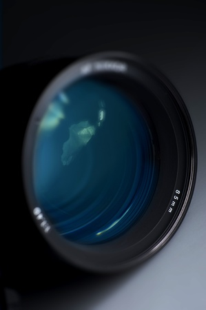 Professional Photography Prime Lens Glass - Blue Light Reflections  Dark Background Vertical Studio Photography   Stock Photo