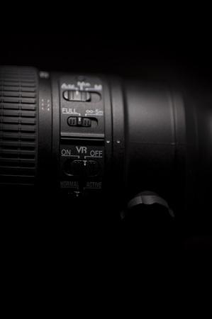 tele: Lens Vibration Reduction - Professional Photography Lens with VR ( Vibration Reduction ) Control Buttons  Switchers Closeup. Black Background - Low Light Vertical Photo.