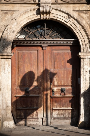 sturdy: Old European Sturdy Wood Doors with Arch  Old City Lighting and Street Signs Shadow  Daylight Vertical Photography  European Architecture   Stock Photo