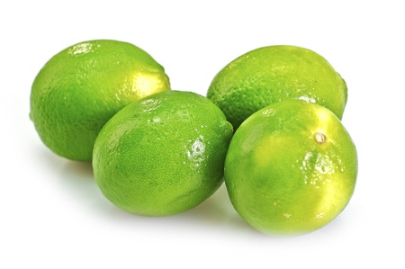 Four Fresh Green Limes Isolated on White  Limes are a good source of vitamin C  Limes are Often Used to Accent the Flavors of Foods and Beverages  Lime Fruits Horizontal Studio Photo