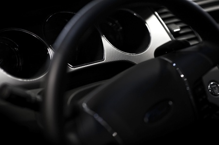 Car Steering Wheel and Dark Black Interior - Vehicle Dashboard  Closeup Photography Stock Photo