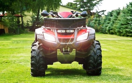 ATV ( All Terrain Vehicle ) - Quad Bike on the Back Yard. Headlights On. Front Shot