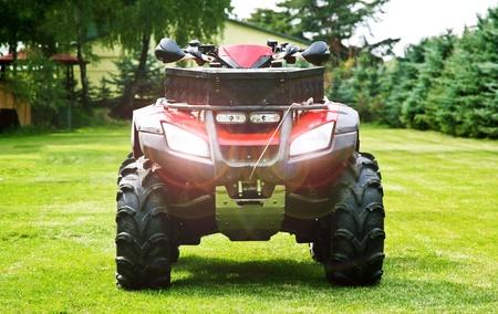 quad: ATV ( All Terrain Vehicle ) - Quad Bike on the Back Yard. Headlights On. Front Shot