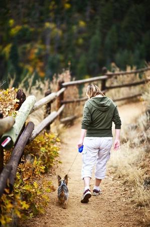 Dog Walk in Colorado. Auf der Spur. Junge Frau mit kleinen Australian Silky Terrier Welpen. Holzzaun und Colorado Landscape. Vertikale Foto. Standard-Bild - 12787628