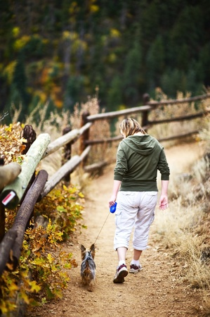 silky terrier: Dog Walk in Colorado. On the Trail. Young Woman with Small Australian Silky Terrier Puppy. Wood Fence and Colorado Landscape. Vertical Photo.