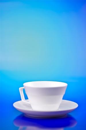 Witter Kleine Cup op Blauwe Achtergrond Verticale Studio Foto