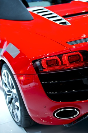 car exhaust: Really Fast Sporty Red Car - Rear Driver Side. Modern Performance Vehicle Closeup. Cars Photo Collection.