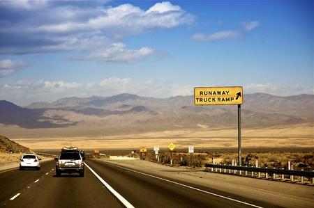 desert highway: Nevada Highway USA. Deserts of Nevada near Las Vegas. Runaway Truck Ramp Large Yellow Sign.