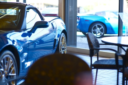 car loans: Sport Vehicles for Sale. Inside Dealership. Two Blue Sport Cars. One Inside and Other Outside.