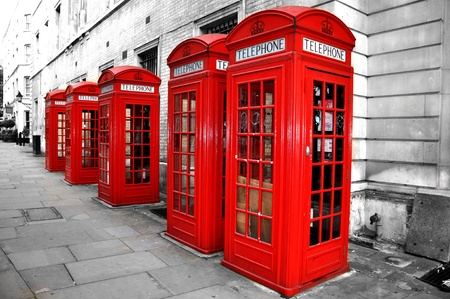 english famous: London Red Telephone Boxes on the Street. Black and White Buildings and Street with Red London Telephone Boxes Stock Photo