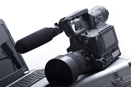 video production: Modern 4 3  MIcro Four-Third  Camera with External Shotgun Microphone and Laptop Computer  35mm Lens - 85mm  Solid White Background  Video Production Theme  Stock Photo