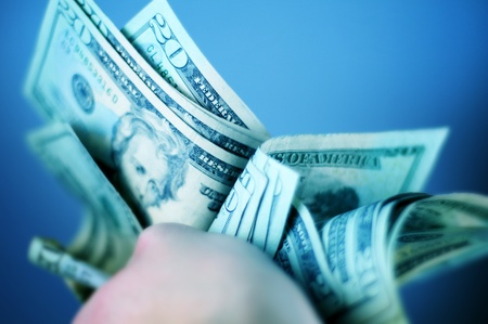 bank owned: Hard Earned Dollars - Twenty American Dollar Bills. Cash in Hand. Bluish Color Theme. Stock Photo