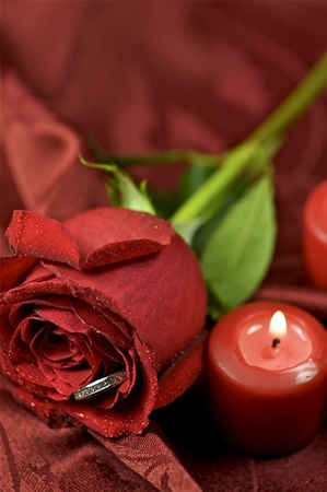Red Rose Engagement Ring. Red Candles and Soft Burgundy Background Fabric