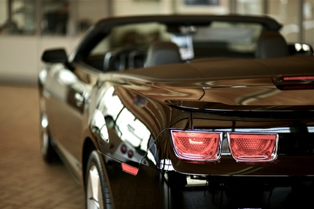 Sporty Convertible Vehicle for Sale. Inside Dealership. Black Performance Vehicle. Rear. Stock Photo