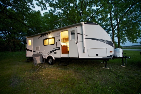 Modern 25 Feet Travel Trailer - Camping in the Forest. Evening/Dusk Photography. Recreation Photo Collection Standard-Bild