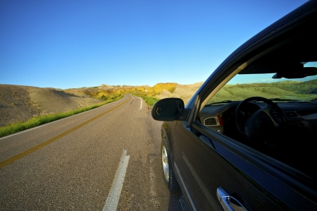 Badlands Drive Thru. Traveling Theme with Black SUV on the Loop Road in Badlands National Park, South Dakota, USA.  photo