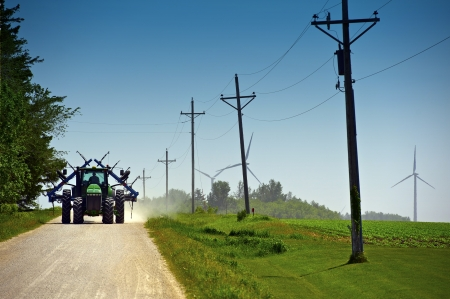 tractors: Minnesota Farmer on Suburb Road Riding Tractor with Farm Equipment. Old Wood Electric Poles and Wind Turbines in a Background. Minnesota, USA. Stock Photo