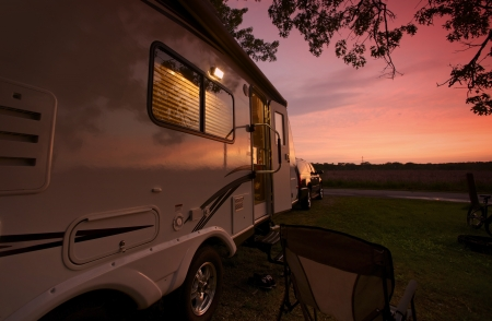 trailer: Travel Trailer in Sunset. Camping in Illinois, USA. Recreational Vehicle. RV Theme. Zion, IL - Illinois Beach State Park, USA. Stock Photo