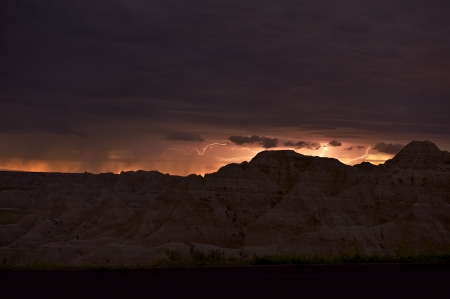 cloude: Storm on the Horizon - Badlands and Summer Storm During Sunset. Badlands Scenery and Beauty of Nature. Nature Photo Collection
