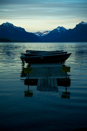 Mountain Lake. Lake McDonald in the Glacier National Park, Montana. Sunset in Glacier. Motorboats on Deck. Mountain Range in Background. Famous Places Photo Collection. U.S. National Parks. Vertical Photography Stock Photo - 14301405