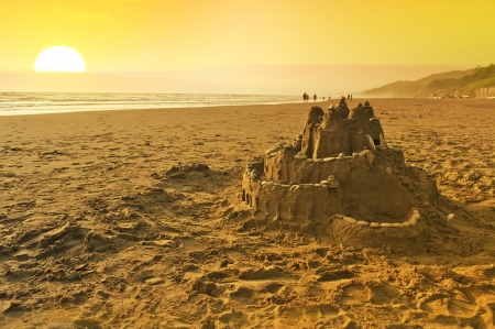 Sand Castle on the Beach. Summer Fun on the Beach of Washington State. Pacific Ocean and the Sunset. Playing with Sand - Sand Castle. photo
