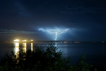 rainstorm: Lightnings in Port Angeles, Washington. Pacific Ocean  Salish Sea. Night Storms and Large Commercial Ship. Severe Weather Photography Collection. Stock Photo