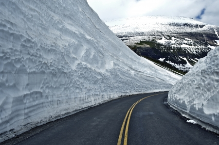 road conditions: Road Thru Snow - Huge Snowfields on Sides of the Road. Glacier National Park - Famous Road-to-the-Sun. Montana, USA. Montana Photography Collection. Stock Photo